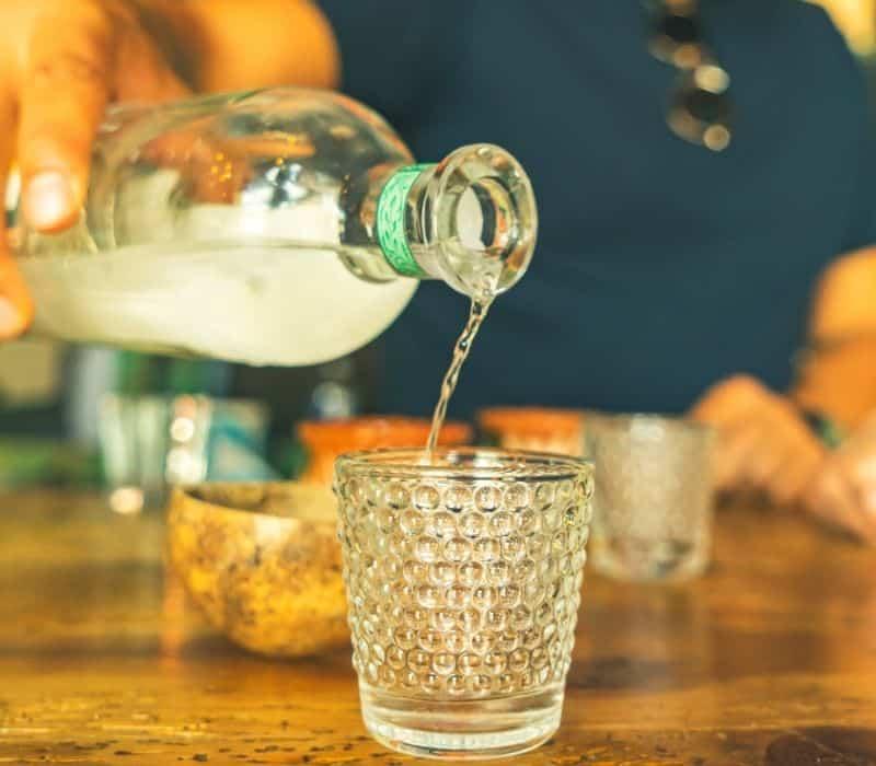 Man pouring mezcal into shot glass