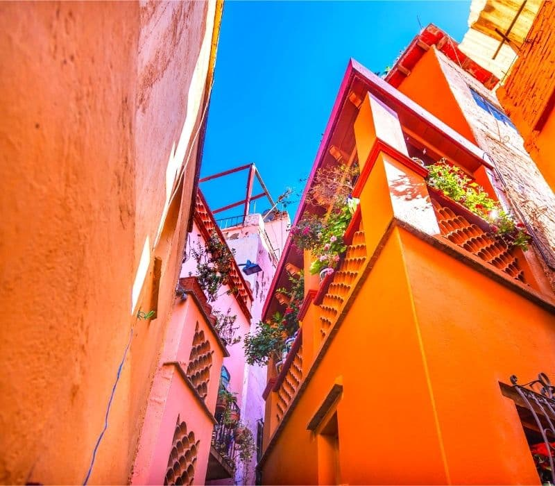 Orange and pink colored buildings with colored balconies