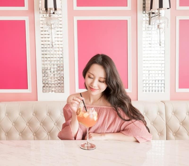 Woman eating alone at a restaurant and drinking an orange beverage