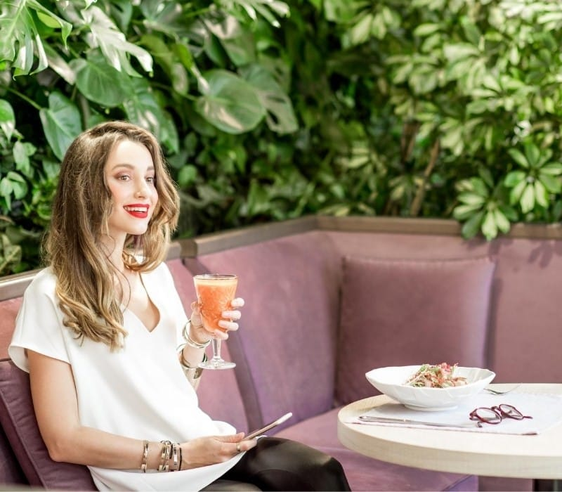 Woman eating alone at a restaurant and drinking an orange drink