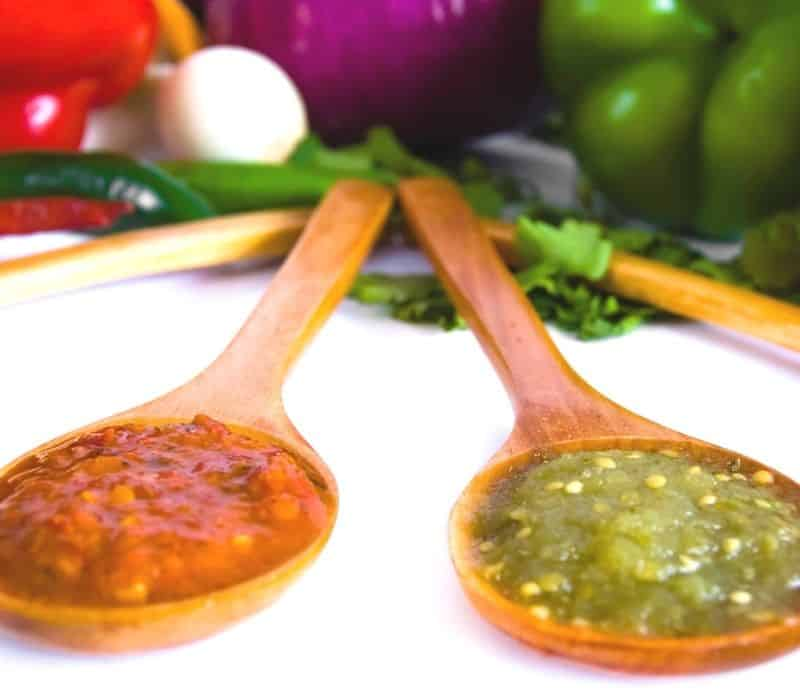 Red and green salsas on tasting spoons