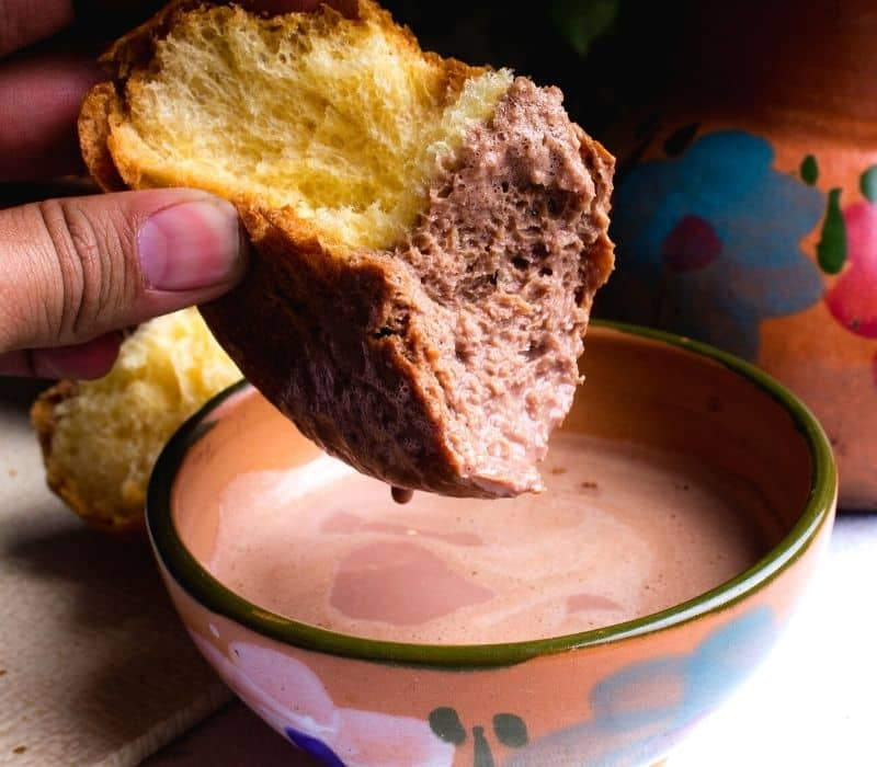 dunking a piece of bread into a cup of hot chocolate - Traveling to Oaxaca