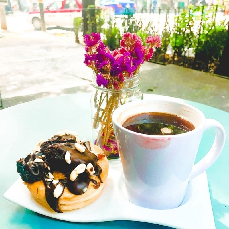 Coffee and donut on a table with purple flowers