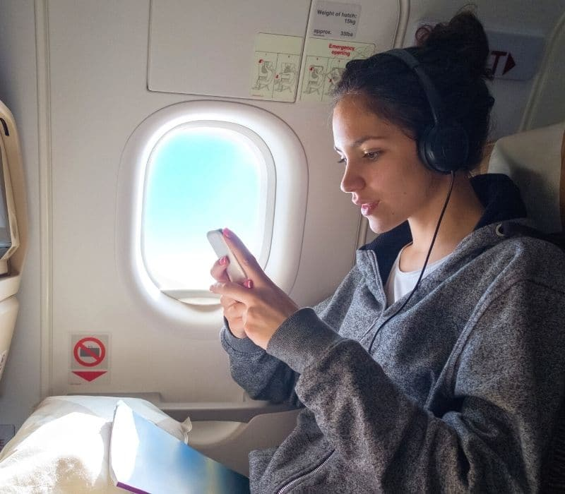 woman on a plane looking at her phone