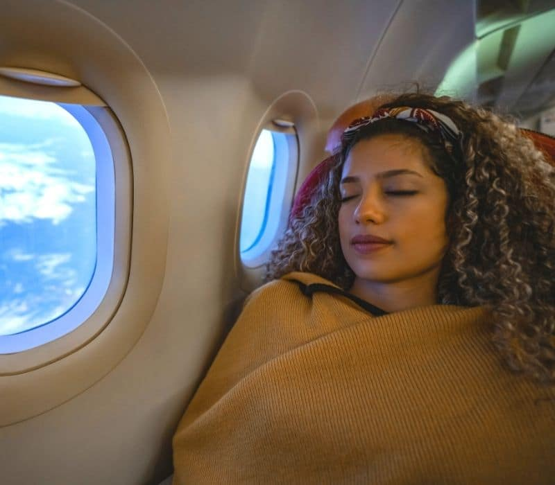 woman traveling solo wrapped in a tan blanket and sleeping on a flight