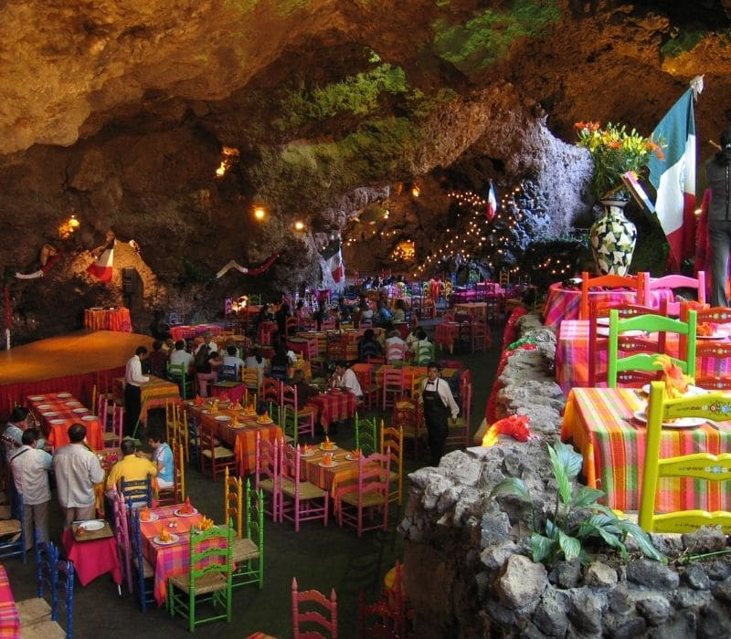 Colorful table and chairs in a restaurant called La Gruta inside of a cave near Mexico City
