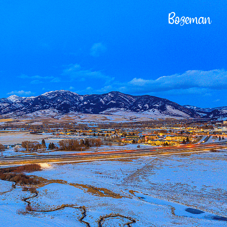 Beautiful shot of Bozeman all lit up at dusk on a snowy day.