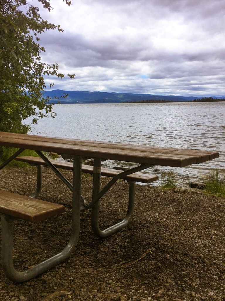 Picnic table by Flathead Lake in Wayfarers State Park near Bigfork, Montana. Visiting Wayfarers State Park is one of the top things to do in Bigfork.