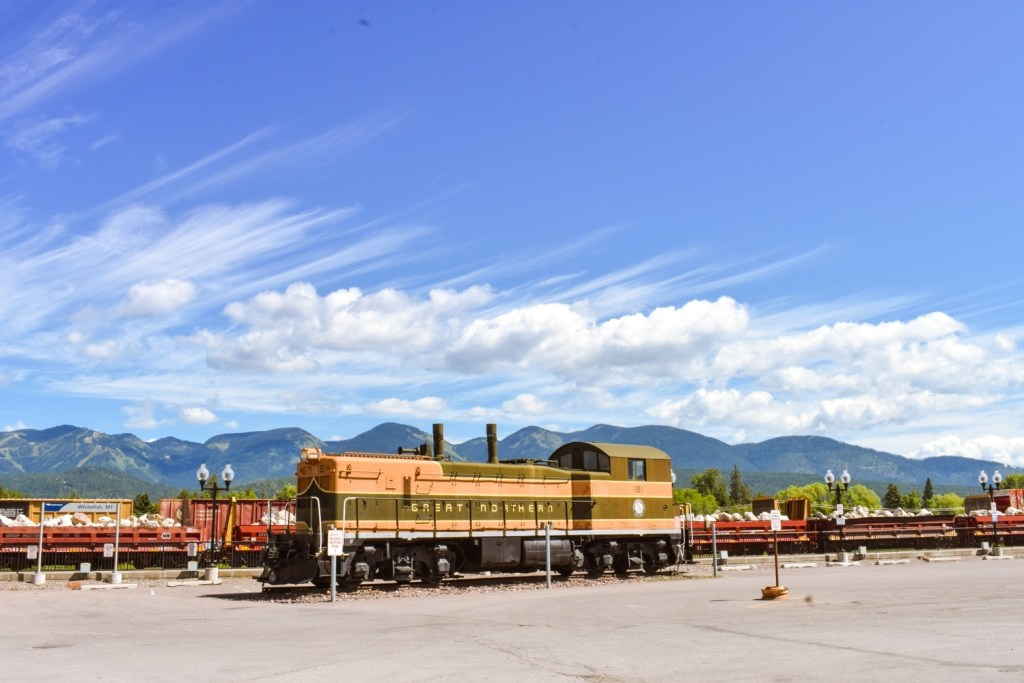 Historic trains with mountains in the background at the Whitefish Depot in Montana near Glacier National Park.
