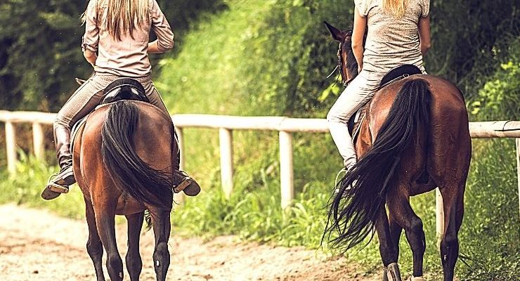 Girls Getaways in Montana that include horseback riding is a quintessential girls trip in Montana! These two women are riding on two brown horses on a ranch trail.