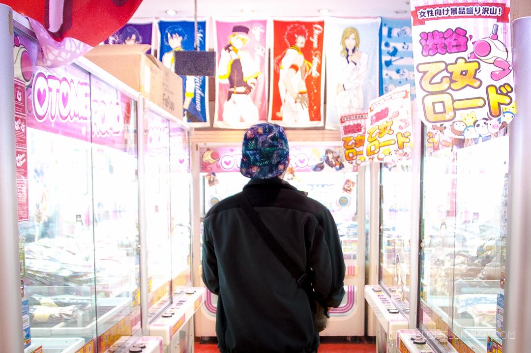 Daniel walking through a bright arcade in Tokyo