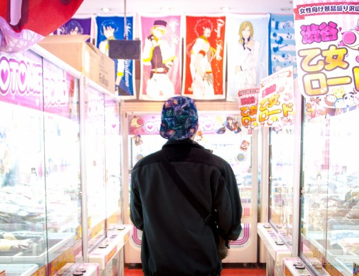 Daniel walking through a bright arcade in Tokyo