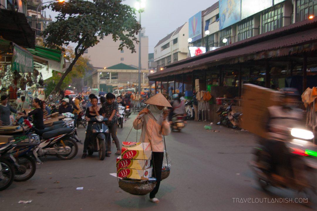 Northern Vietnamese Street Food - Woman carrying balancing bar in Hanoi night market