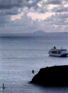Cruise ship entering English Harbor. Island of Montserrat is in background