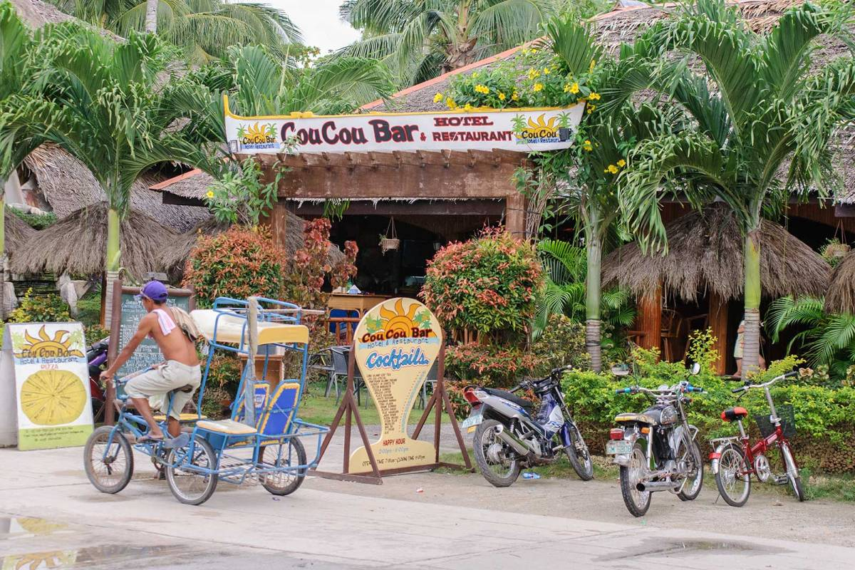 A pedicab driving by Cou Cou Bar, Hotel & Restaurant