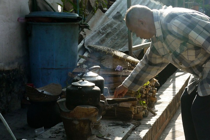 An elderly man stokes and tends the breakfast fires in Luang Prabang, Laos.
