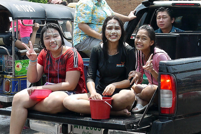 Talc powder on the face as they women prepare to soak the next closest reveler during Songkran in Chiang Mai, Thailand
