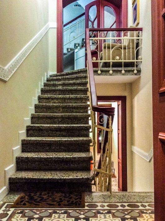 Ανεβαίνοντας τα σκαλιά της εισόδου του ατμοσφαιρικού ξενοδοχείου εποχής Gatto Perso