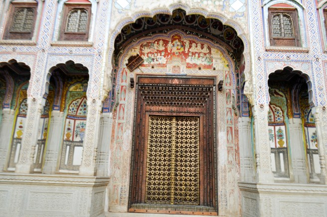 An intricately carved door at the entrance of a haveli