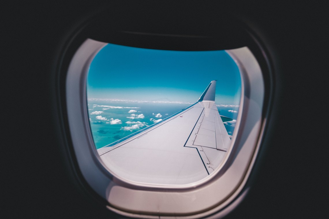A photo taken through an airplane window on the way to start a year abroad, looking out over the plane wing. The inside of the plane is dark while the outside sky is bright blue.