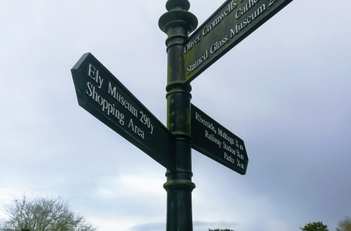 A view of a signpost in Ely, with signs pointing to the Cathedral and town