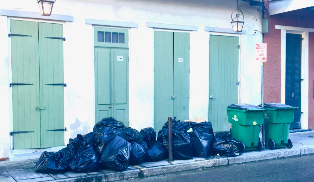 Mornings in NOLA: Garbage is piled by the curb each morning. It will be cleared away long before the day's visitors appear. (Photo by Suzanne Ball. All rights reserved.)