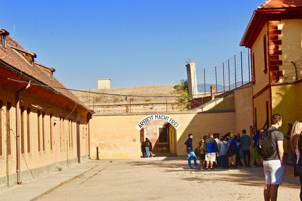 "Terezin had the ritual concentration camp slogan ""Arbeit Macht Frie"" over the entry. ""Work sets you free"" was a mockery for the prisoners. Admistrative offices line the courtyard to the entry."