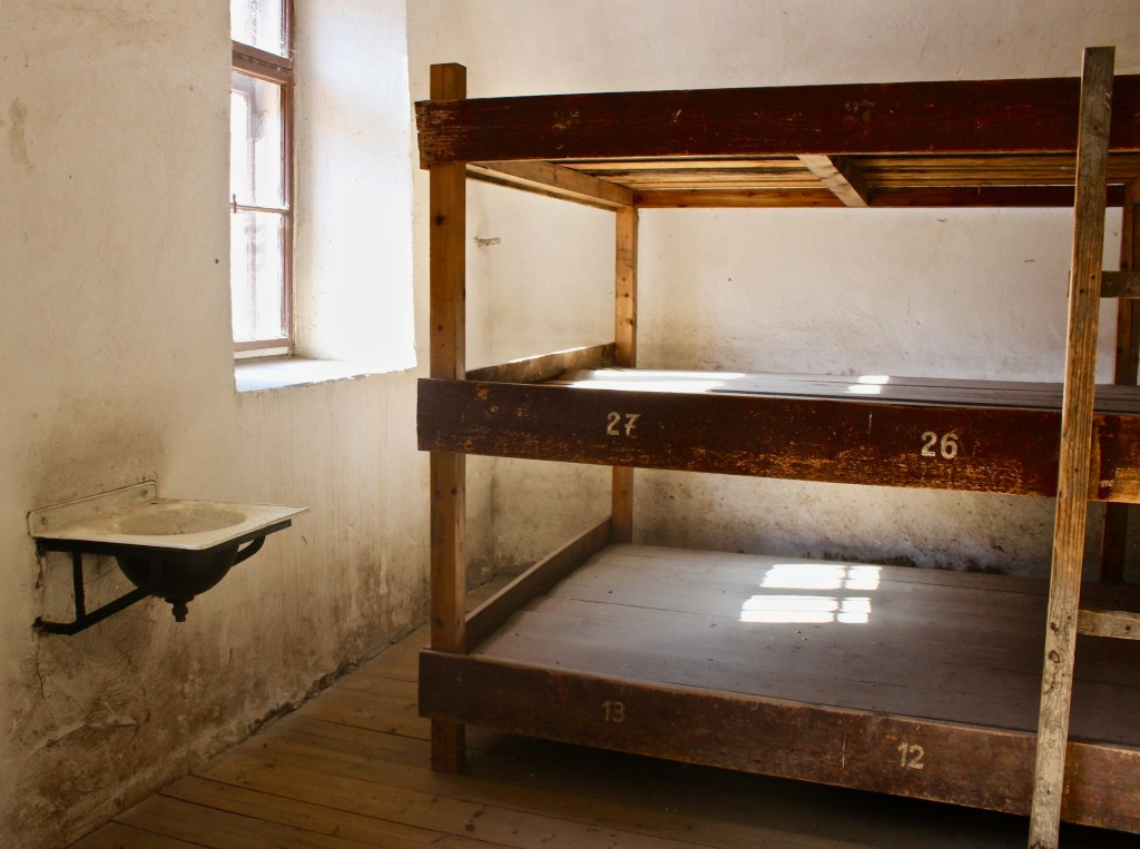 About 90 Terezin prisoners shared a room, with one toilet and one sink. They ate meager meals at narrow tables in the room.