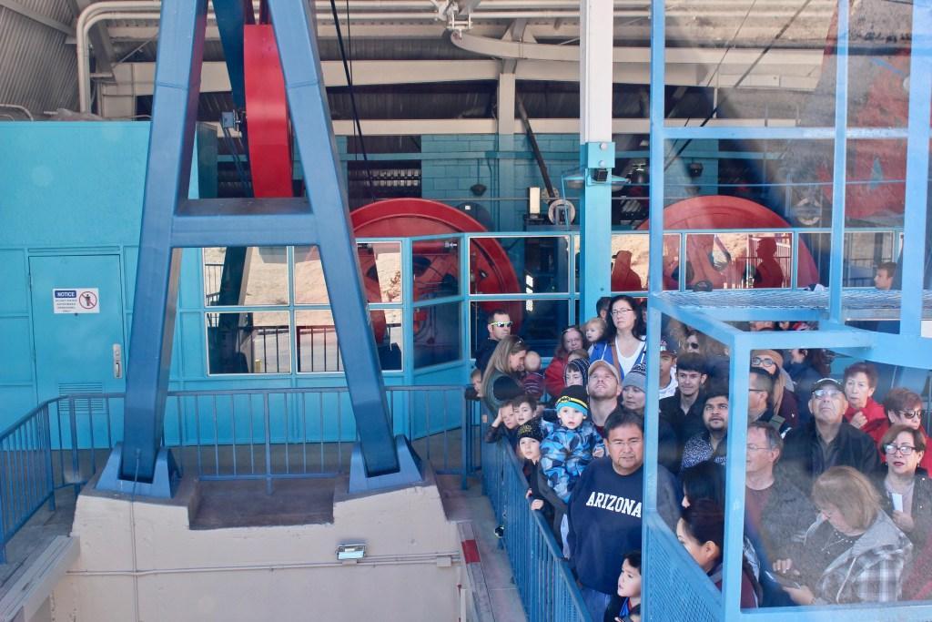 "Future passengers await their ""flight"" as the tram returns to the lower terminal."
