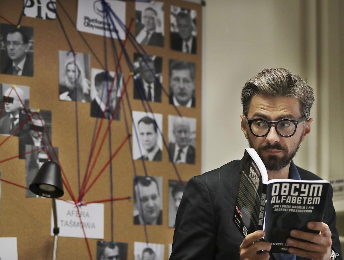 Grzegorz Rzeczkowski, an investigative reporter for the weekly Polish newsmagazine Polityka, poses with a book he has written about an eavesdropping affair that helped toppled a government, in Warsaw, Poland, June 28, 2019.