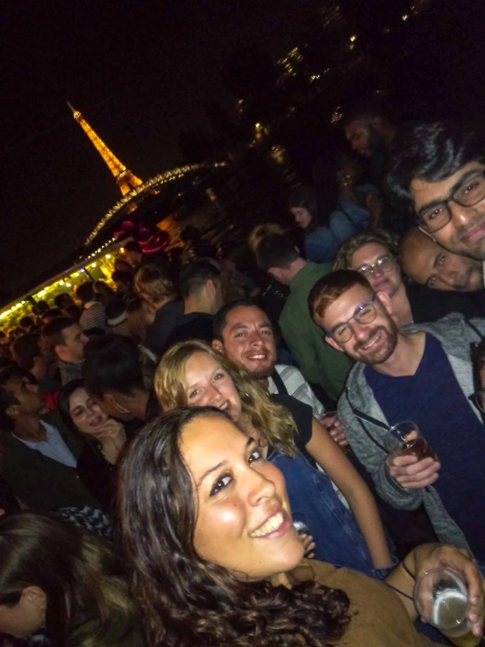 Couchsurfing boat party on the Seine in Paris France in front of the Eiffel tower.
