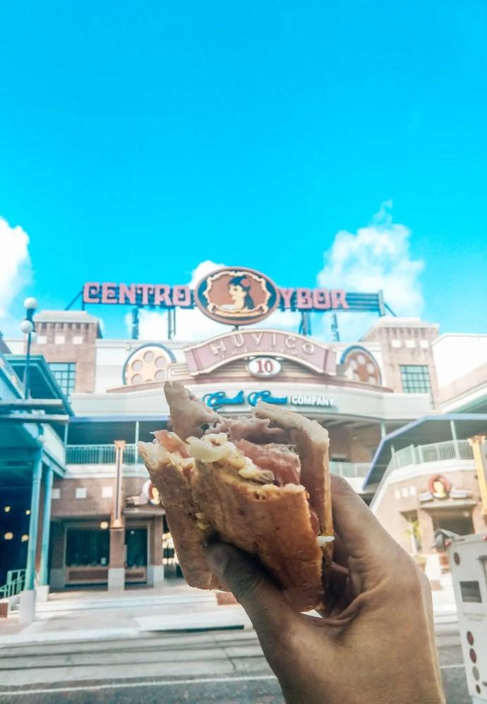 Cuban sandwich from Segunda Bakery in front of Ybor City Sign.