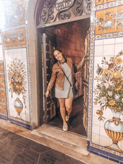 Sarah Fay in the doorway of Columbia Restaurant in Ybor City, Tampa, Florida. A colorful entry way that's tiled.