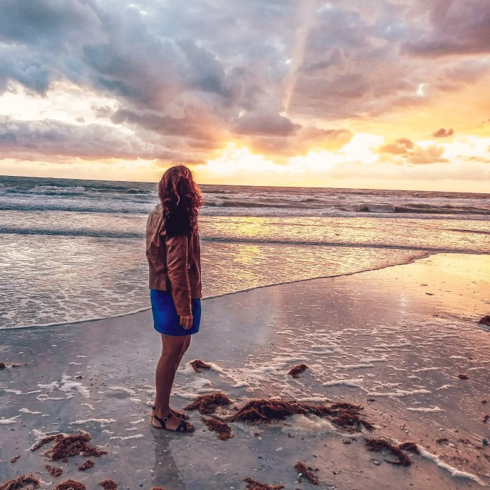 Sarah Fay travel blogger admiring the sunset in Clearwater Beach. The Sky looks like cotton candy.