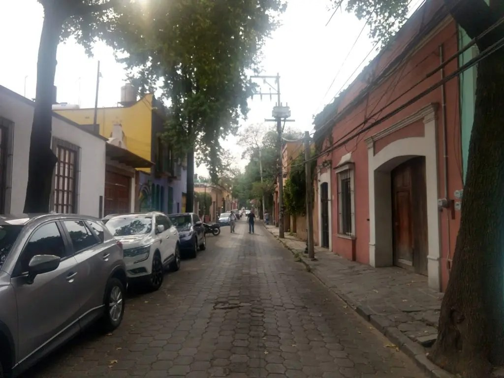 street in Coyoacán  with many pastel colored buildings.