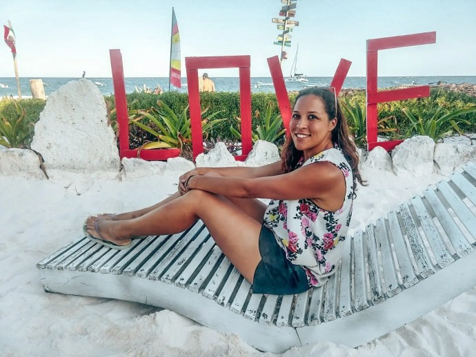 Love Tulum red sign with Sarah Fay on a sun bed on tulum beach