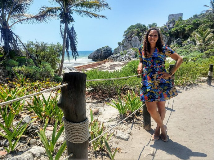 Sarah Fay travel blogger in front of the Tulum Beach and Ruins  on sunny day.