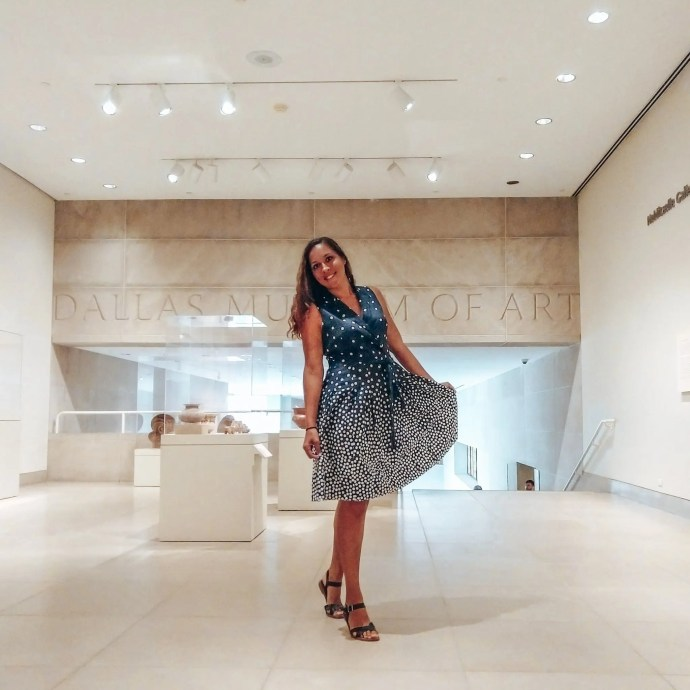 Sarah Fay travel blogger inside the Dallas Museum of Art in a blue navy dress with white dots.