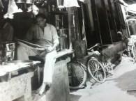 Shopkeeper reading in the doorway in the early morning light in Banaras (Varanasi), India.