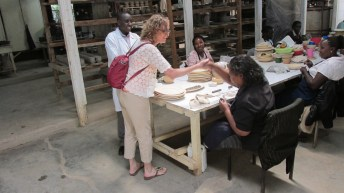 Me shaking hands with woman and store where women hand make jewelry and pottery.