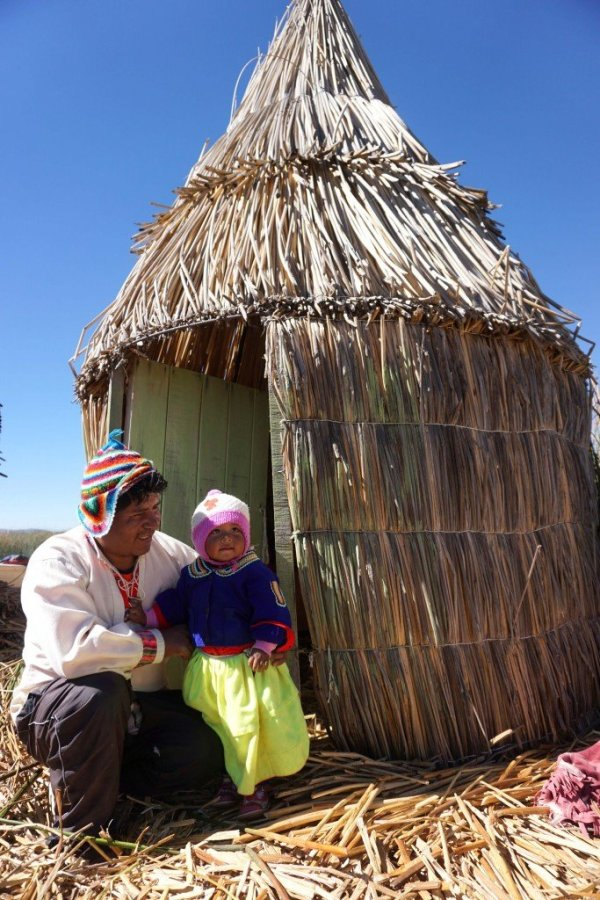 Father and young daughter in formnt of one of their buildings on the floating island