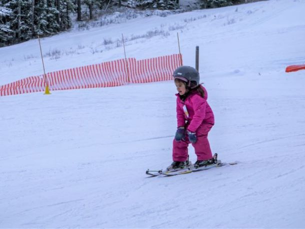 child skiing in pink snowsuit at Mount Norquay