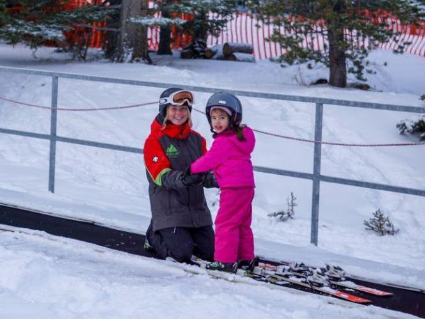 Ski instructor and child on magic carpet Mount Norquay