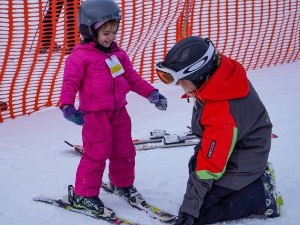 downhill ski instructor in front of girl in pink jacket