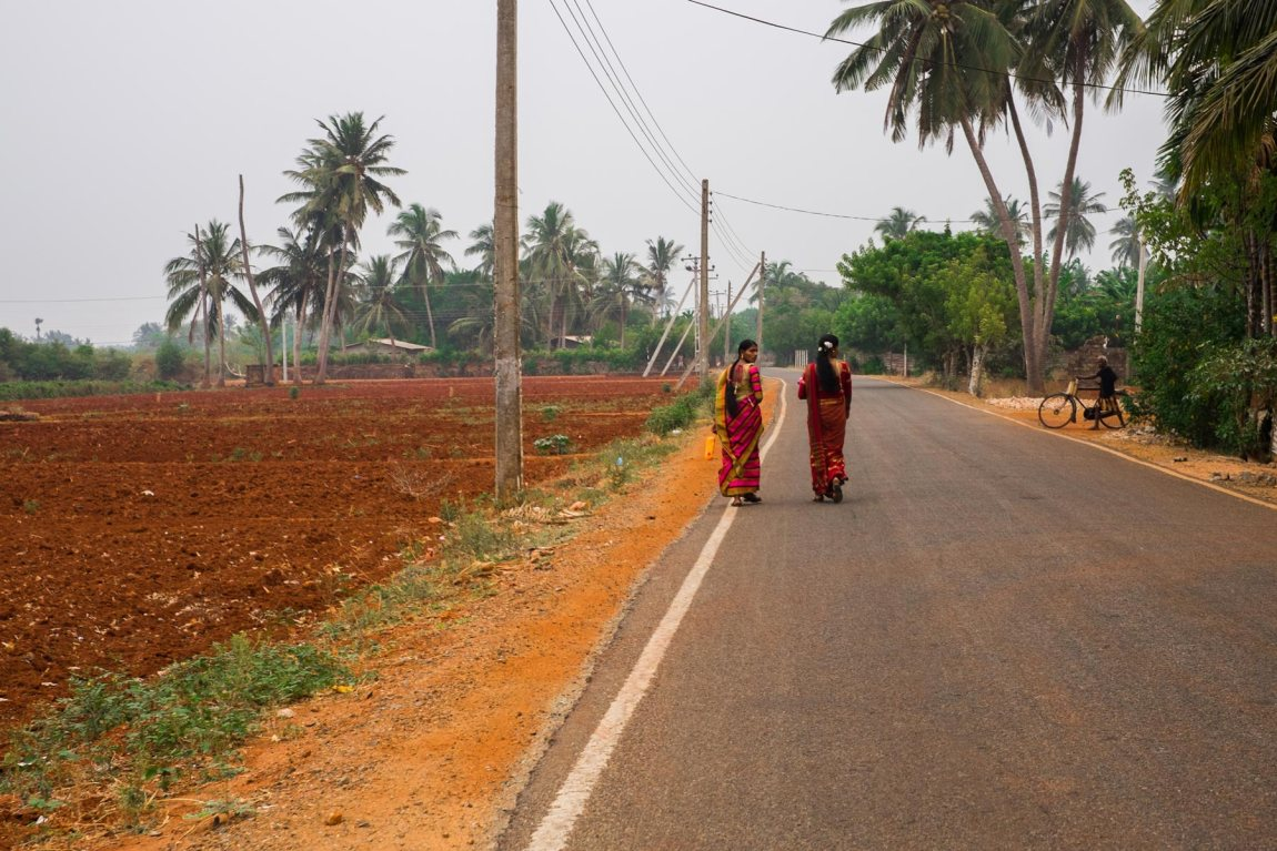 Women in red saris walk along the road in Jaffna District.