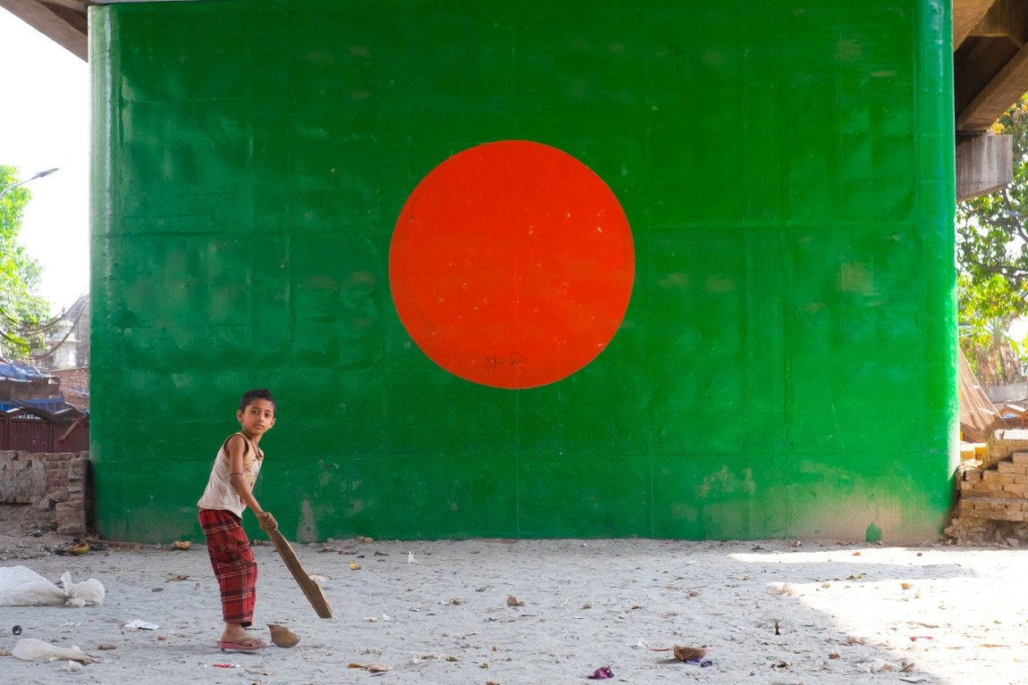 A boy plays cricket in front of a mural of the Bangladeshi flag painted on a wall in Dhaka.
