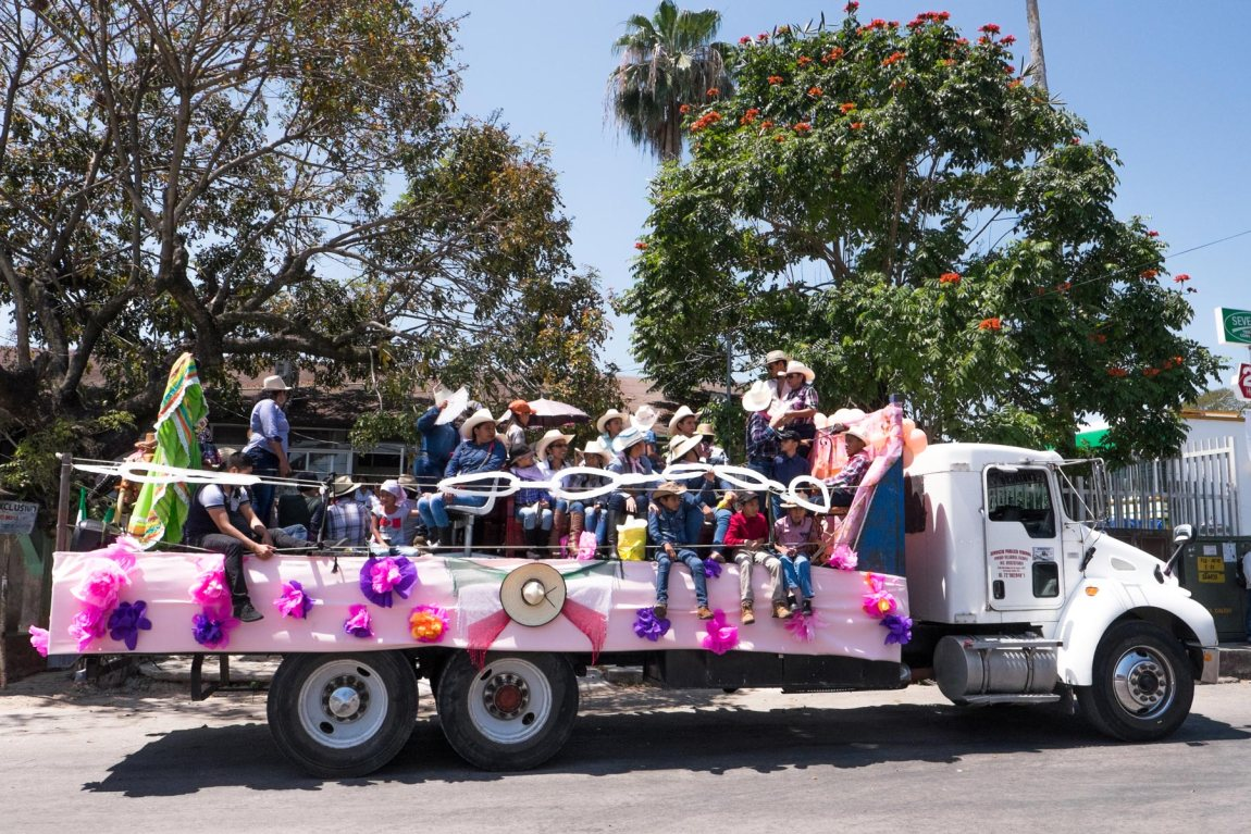 A decorated truck filled with cowboys and cowgirls on a Mexico street.