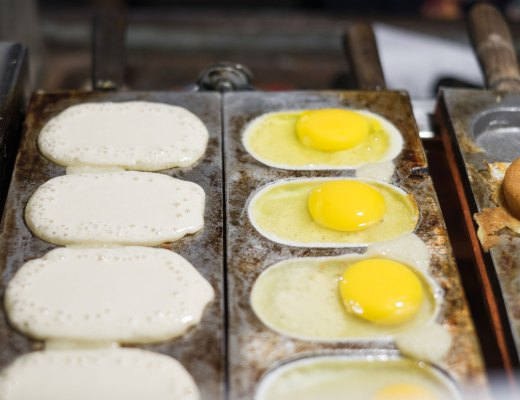 Egg buns cooking in metal molds in Bangladesh