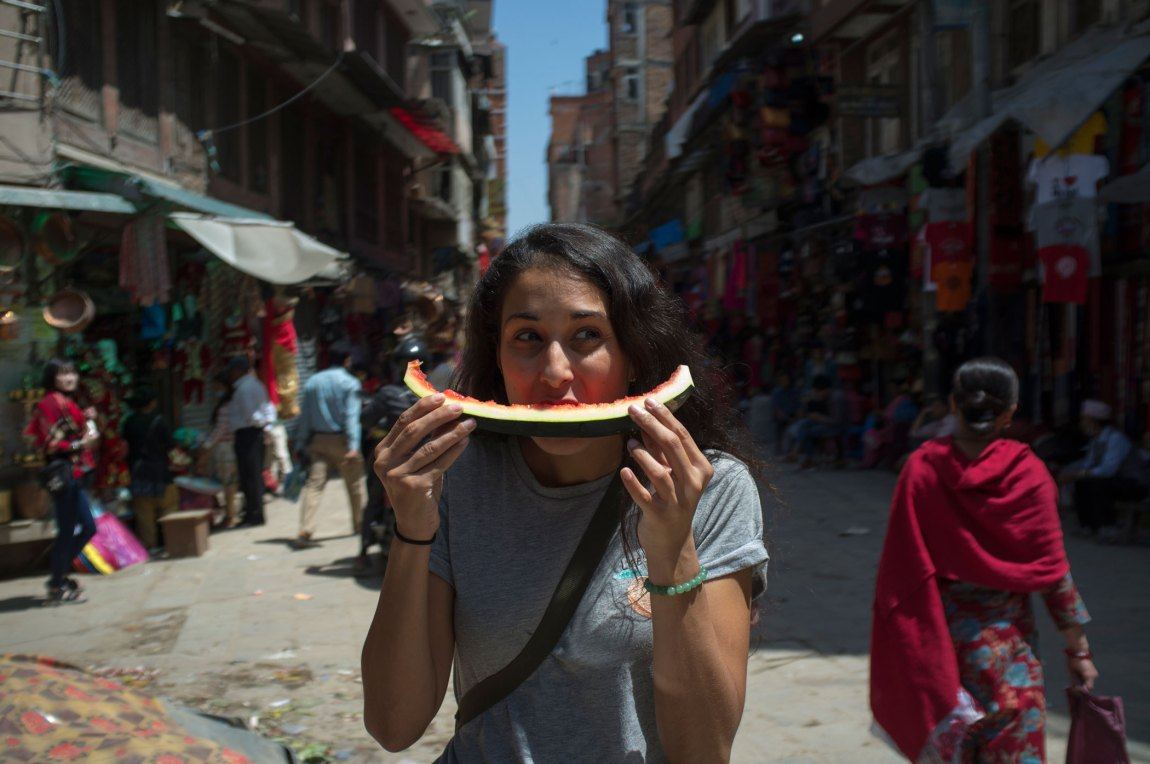 A woman eating a piece of watermelon on the street.