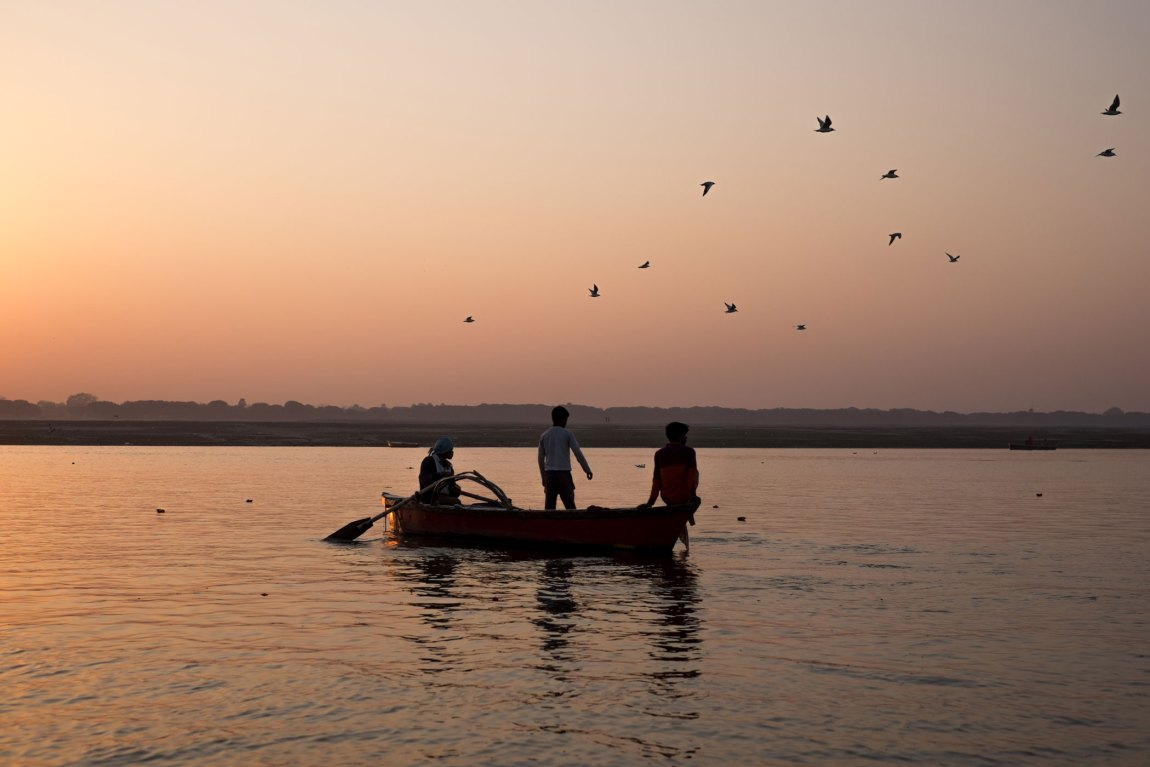 Three men fishing on a boat on the Ganges river in Varanasi